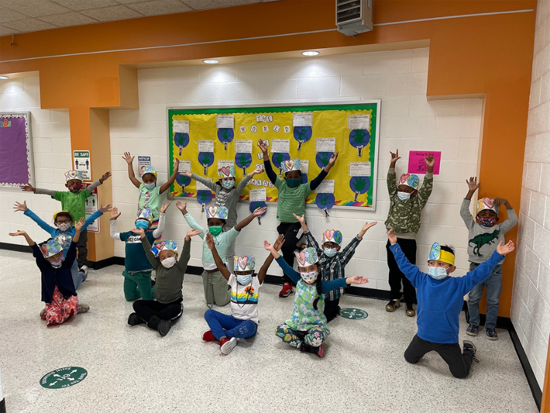 Kindergarten students putting their hands in the air for Earth Day